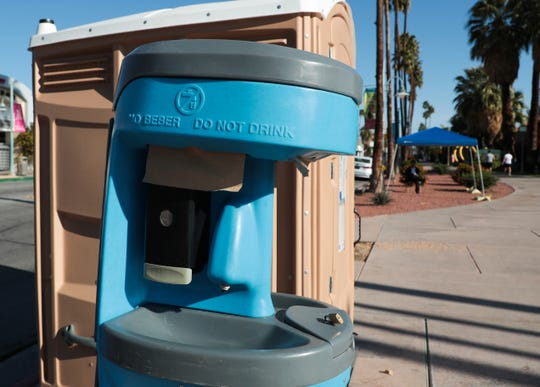 A portable restroom and hand washing station sit near the intersection of E Alejo Road and N Palm Canyon Drive in downtown Palm Springs, Calif. on Sunday, March 29, 2020 as a precautionary measure during the coronavirus outbreak.