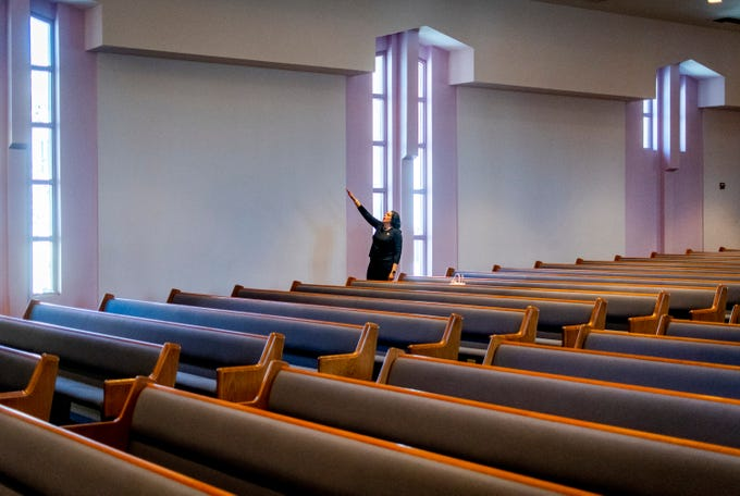 Rev. Karen Stewart waves her hands in prayer and song during a live-streamed Sunday service at First Institutional Baptist Church in Phoenix on March 29, 2020. The service focused on adapting to the many changes the coronavirus pandemic has brought.