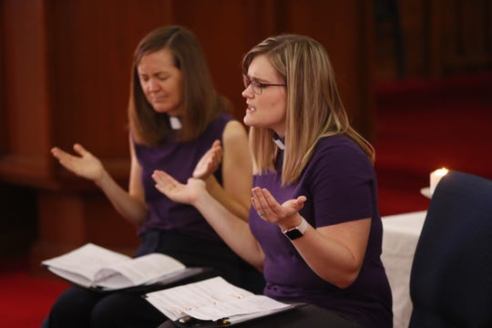 Pastor Sarah Stadler (Left) and Vicar Beth Gallen pray for people affected by the coronavirus during the Sunday service at Grace Lutheran Church in Phoenix on March 29, 2020.