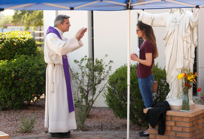 Father Eduardo Montemayor prays with Erin Monnin during confessions hosted outside to conform with social distancing and prevent COVID-19 spread at Most Holy Trinity Parish in Phoenix on March 28, 2020.