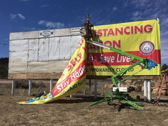"""Workers put up a billboard that advertises the Navajo Nation's """"stay at home"""" order as well as practice social distancing in response to COVID-19."""