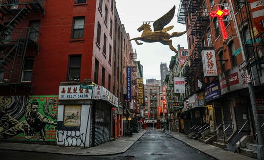 """A street in New York's Chinatown is empty, the result of citywide restrictions calling for people to stay indoors and maintain social distancing in an effort to curb the spread of COVID-19, Saturday March 28, 2020, in New York. President Donald Trump says he is considering a quarantine affecting residents of the state and neighboring New Jersey and Connecticut amid the coronavirus outbreak, butNew York Gov. Andrew Cuomo said that roping off states would amount to """"a federal declaration of war."""" (AP Photo/Bebeto Matthews)"""