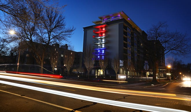As traffic streaks past, patriotic lights of red, white and blue illuminate the side of the Strathallan Rochester Hotel & Spa on East Ave. in downtown Rochester Friday, March 27, 2020 in a show of support for the city and the country during the coronavirus pandemic.