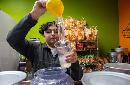 David Cervantes, pours water into a plastic cup for a few customers late Saturday evening at their Capitola location. David's parents are the proud owners of Bella Fruit & Drinks. David has been a part of their business since he was 5-years-old.