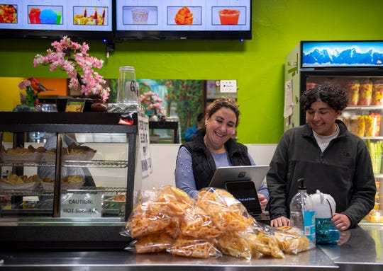 Cristina Bernal Cervantes, left, laughs with her son David Cervantes, as they both stand behind the register of their Capitola business on Feb. 22, 2020.