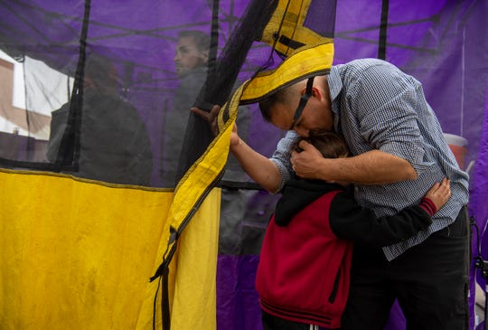 Juan Carlos Cervantes holds his son before the start of the Salinas Farmers Market on Feb. 21, 2020.