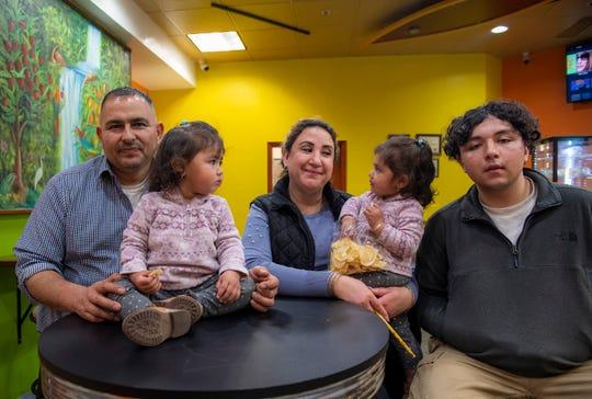 Juan Carlos Cervantes, left, Cristina Bernal Cervantes, middle, and David Cervantes get their photo taken as a family inside Bella Fruit & Drinks in Santa Cruz on Feb. 22, 2020.
