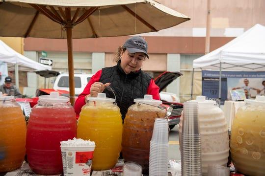 Cristina Bernal Cervantes, co-owner of Bella Fruit & Drinks helps arrange the water jugs before the start of the Salinas Farmers Market on Feb. 22, 2020.