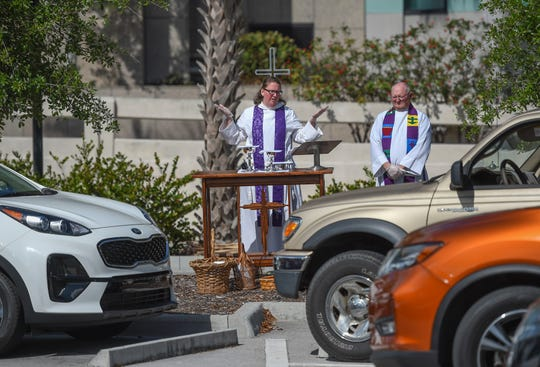 """Reverend Amy Turner (center) of St. Andrew's Episcopal Church prepares for communion alongside of Rev. John Liebler, of St. Simon the Cyrenian Episcopal Church, during their drive-in Eucharist service in the parking lot of St. Andrew's on Sunday, March 29, 2020, in Downtown Fort Pierce. The unconventional service provided for a safe environment for parishioners of both churches due to the COVID-19 pandemic, by broadcasting the sermon on FM radio 101.1. """"You can see people waving to each other, talking to each other in the distance, there is a sense of community,"""" Rev. Liebler said."""
