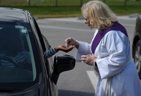 Reverend Sharon Britcher, of St. Andrew's Episcopal Church, hands out wafers with protective gloves for communion during the drive-in Eucharist service in the parking lot of St. Andrew's on Sunday, March 29, 2020, in Downtown Fort Pierce