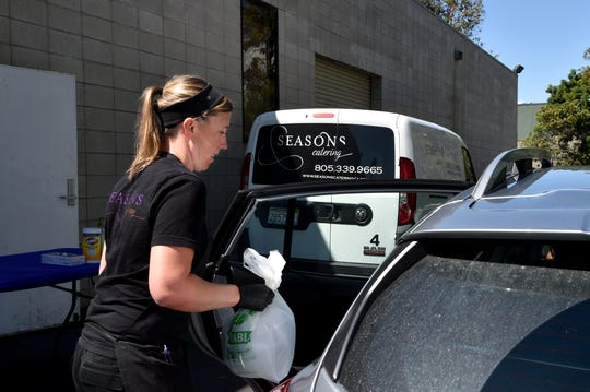 Michelle Osbourne, chef de cuisine at of Seasons Catering in Ventura, delivers an order to a customer's vehicle on March 27. The community store project has since been paused as Seasons Catering teams with World Central Kitchen to help feed hospital staff battling the COVID-19 crisis.