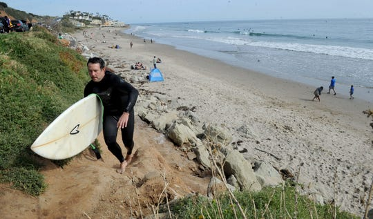A surfer walks up from County Line beach before the recent closure.