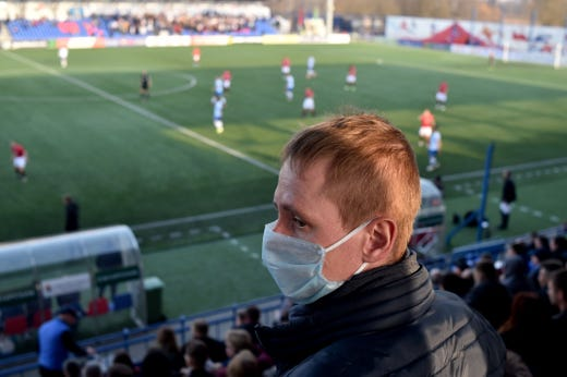 A supporter of FC Minsk, wears a facemask for protective measures amid concerns over the spread of the COVID-19, as he attends the Belarus Championship football match between FC Minsk and FC Dinamo-Minsk in Minsk, on March 28, 2020.