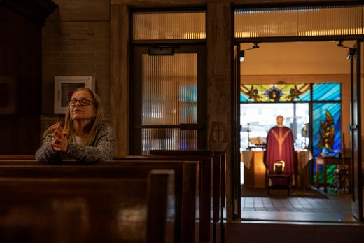 Fran DiBiasio sits alone in Our Lady of Grace Catholic Church as Rev. Peter Gower celebrates Mass from the front door as worshippers listen over the radio from their cars in the parking lot, Sunday, March 29, 2020, in Johnston, R.I.