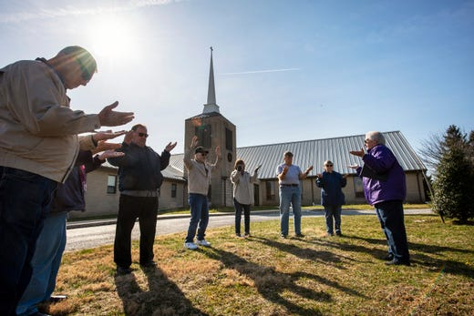 The Rev. Lou Ann Jones, right, leads prayer as eight people spread out around the flagpole at St. John's Blymire's United Church Of Christ near Dallastown, Pa. on Wednesday March 16, 2020 and prayed for the community, nurses and doctors, government leaders and many others during the turmoil from the coronavirus pandemic.