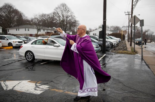 Reverend Peter Gower walks out to the parking lot to spread incense to worshippers sitting in their cars during a Mass he holds from the front door of Our Lady of Grace Catholic Church, Sunday, March 29, 2020, in Johnston, R.I.