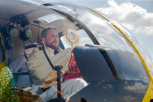 Father Richard Pagano sits in the cockpit before offering Benediction to his Church and St. Augustine, Fla. surrounding areas during a helicopter flyover for the Coronavirus Pandemic.
