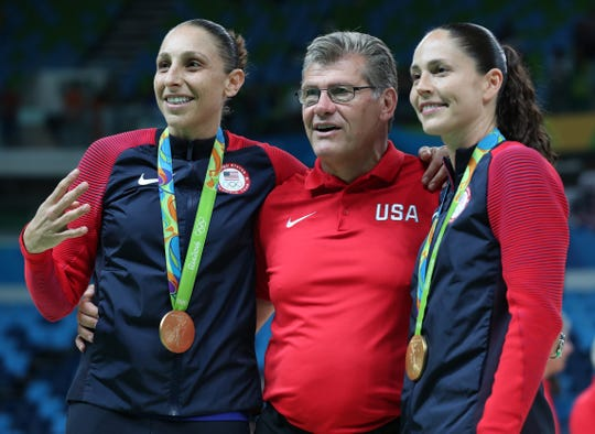 Diana Taurasi and Sue Bird pose for a picture with head coach Geno Auriemma after beating Spain in the 2016 women's basketball gold medal game.