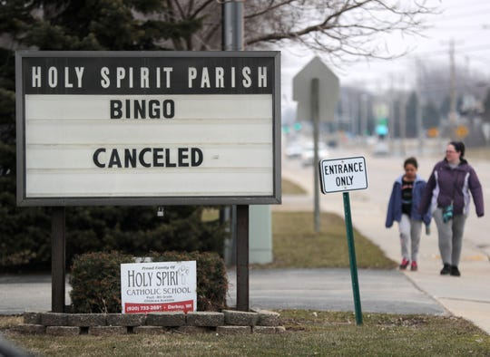 Pedestrians walk past a sign announcing the cancellation of bingo at Holy Spirit Parish on Monday, March 23, 2020, in Darboy.