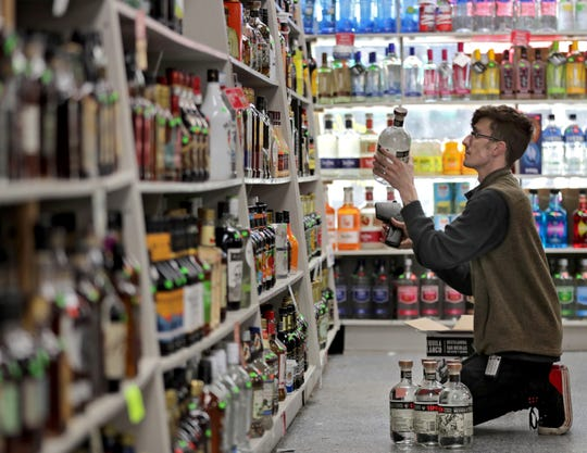 Deaven Stermer stocks shelves at Flanagan's Stop and Shop in anticipation of the closing of the city's bars and restaurants at 5:00 p.m. on Tuesday, March 17, 2020 in Appleton.  Wm. Glasheen USA TODAY NETWORK-Wisconsin