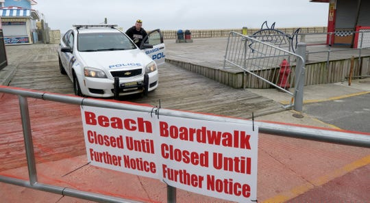 A Seaside Heights police officer drives off the boardwalk through a barrier closing access at Grant Avenue Monday, March 30, 2020.