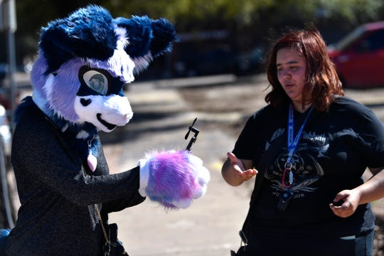 Ryan Ekberg holds a smartphone-powered fan given to her by Natasha Kuhn to cool her off inside the mask Wednesday. Ryan came downtown hoping to cheer up any who might have been looking for an escape.