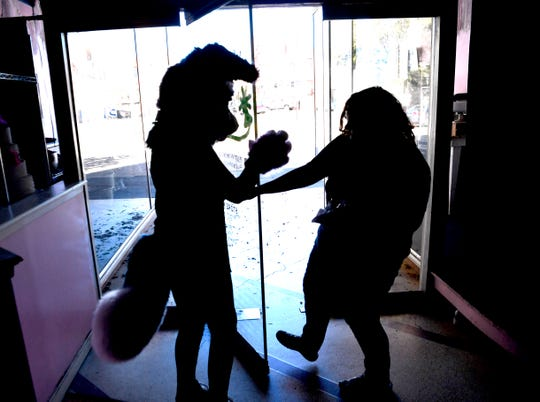 Natasha Kuhn helps her friend Ryan Ekberg exit McKay's Bakery downtown Wednesday. Ryan's furry costume comes with a blindspot in the center, necessitating the need for a spotter on excursions like this.