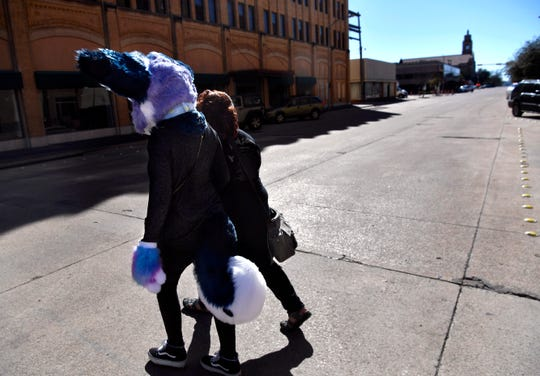 """Ryan """"Tokyo"""" Ekberg and her friend Natasha Kuhn cross North 3rd Street while walking down Cypress back to their car Wednesday. Tokyo is Ryan's """"Furry"""", a costumed character based on a husky she created for fun."""