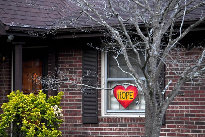 """A home is East Asheville displays a heart with the word """"hope"""" in the window as the nation copes with the spread of novel coronavirus on March 27, 2020."""