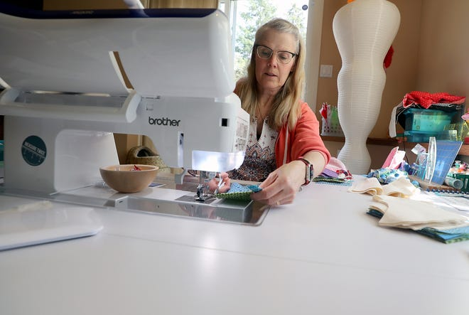 Sarah Lewis, of the Kitsap Quilters Guild, sews masks for healthcare workers in her Brownsville home on Monday. Efforts by many sewers and sewing groups across the Kitsap Peninsula have resulted in hundreds of sewn masks that have been donated to Harrison Medical Center, long-term care facilities and doctors' offices.