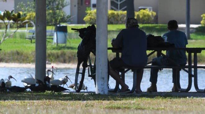 Men sit alongside the lake at Wells Park up the street from The Daily Bread in Melbourne. As concerns over the coronavirus grow, The Daily Bread's kitchen still offers take-out meals for clients, some of whom are homeless, or outdoor dining with seating spaced out for social distancing between 11 a.m. and 1 p.m.