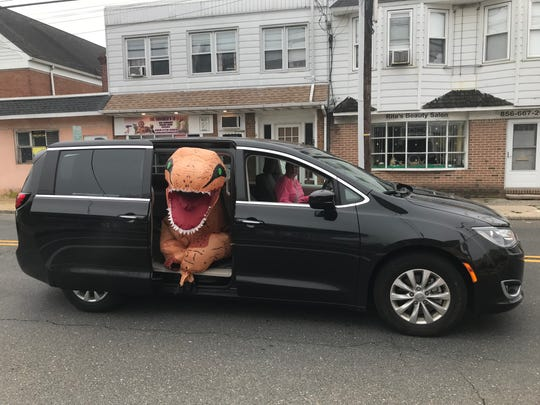 Amanda Smalley of Maple Shade wears a dinosaur costume while taking part in birthday parades in Maple Shade.