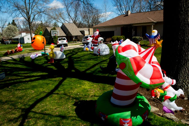 A view of inflatable decorations, including the Easter Bunny and Santa Claus, adorn a yard in Wyoming, Ohio, on Monday, March 30, 2020.