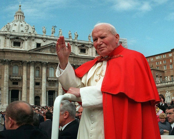 Pope John Paul II waves to the faithful April 23, 1997, as he crosses St. Peter's Square at the Vatican. Pope Francis has cleared John Paul II for sainthood.