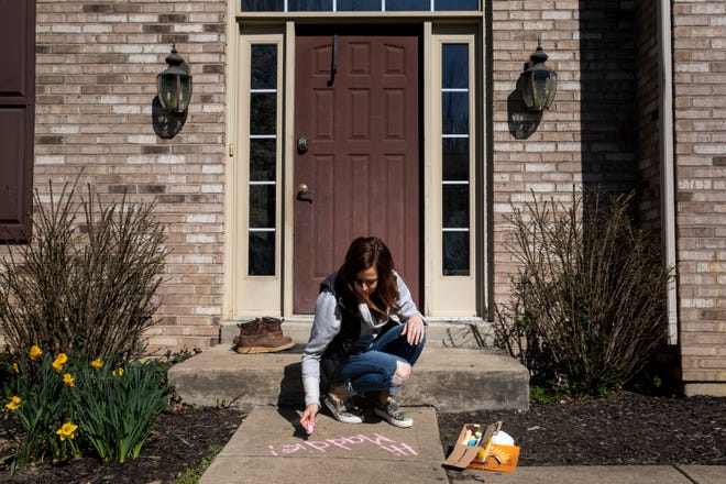 Kindergarten teacher Amy Clyde writes a message to her student on their sidewalk in Cleves on Monday, March 30, 2020. Clyde teaches at Our Lady of Visitation.