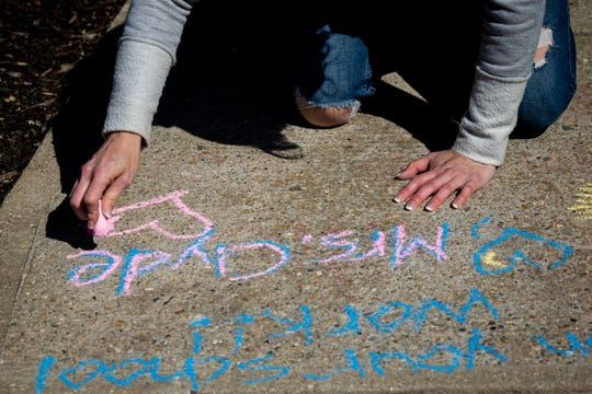 Kindergarten teacher Amy Clyde writes a message to her student on their sidewalk in Cleves on Monday, March 30, 2020.