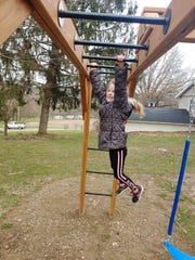 Tatum Lowe, 7, stays active on monkey bars part of a junior ninja obstacle course. Her mother, Rachelle Lowe of Kids America, said it's important for kids still get outside and play during the current stay at home order and for parents to be right there with them.