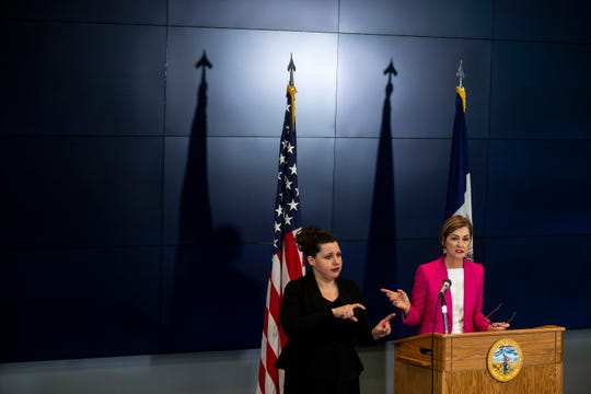 Tailyn Kaster, a sign language interpreter from West Des Moines, stands next to Iowa Governor Kim Reynolds, interpreting her daily new conference updates about COVID-19 in the state, on Sunday, March 29, 2020, at the State Emergency Operation Center in Johnston.