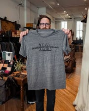 Fontenelle Supply Co. co-owner Erich Bockman holds a screen-printed T-shirt. The proceeds of the T-shirt sale will go to support East Village businesses.