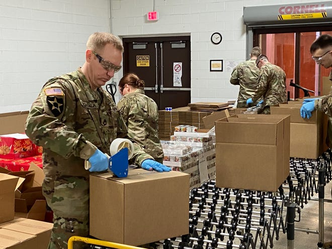 Members of the Michigan National Guard pack food to be distributed to families during the coronavirus crisis at the Food Bank of Eastern Michigan in Flint.