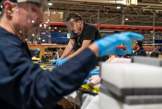 Michael Pandori, center, assembles protective face shields Friday at Troy Design and Manufacturing, a Ford subsidiary in Plymouth. Ford, in cooperation with the UAW, will assemble more than 100,000 critically needed plastic face shields per week to help medical professionals, factory workers and store clerks.