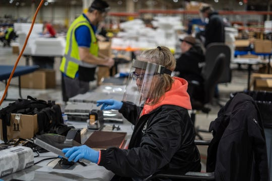 Pat Tucker works on assembling protective face shields on March 27 at Troy Design and Manufacturing, a Ford subsidiary, in Plymouth. Ford, in cooperation with the UAW, has reached its goal of 1 million face shields within 13 days to help medical professionals, factory workers and store clerks.