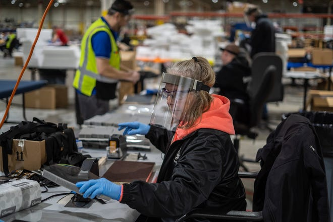 Pat Tucker works on assembling protective face shields at Troy Manufacturing Design a Ford subsidiary in Plymouth on Friday, March 27, 2020. Ford, in cooperation with the UAW, will assemble more than 100,000 critically needed plastic face shields per week to help medical professionals, factory workers and store clerks.