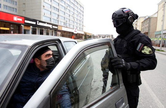 A police officer wearing a protective mask and glasses stops a car driver to check his documents in Grozny, Russia, Monday, March 30, 2020.