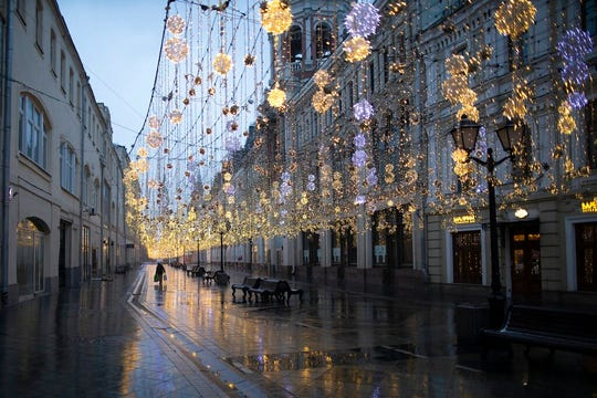 A lone figure walks along empty Nikolskaya street with a lot of bars, cafes and shops closed for now in Moscow, Russia, Monday, March 30, 2020. Russian President Vladimir Putin says the country has managed to slow down the spread of coronavirus but should be prepared for contagions to quickly grow.