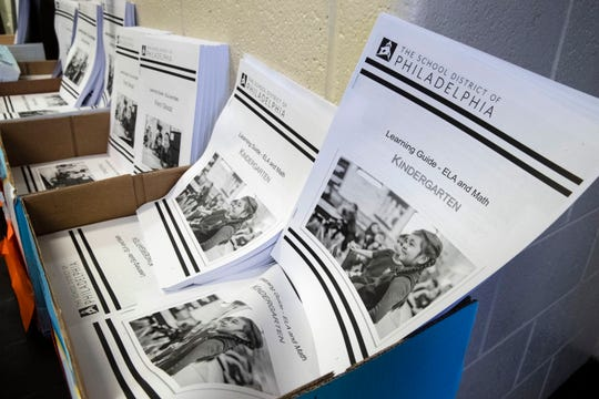 In this Wednesday, March 25, 2020, photo are learning guides to be distributed to students at John H. Webster Elementary School in Philadelphia.