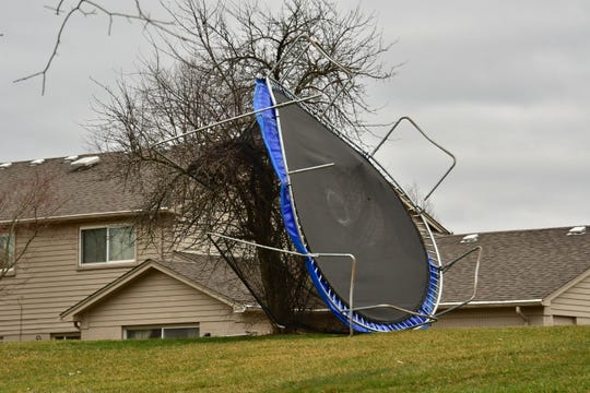 A trampoline is tangled in a tree in the backyard of a home on Applewood Lane near 14 Mile in Farmington Hills on Sunday. Winds reached gusts of up to 62 in the state, the National Weather Service reported.