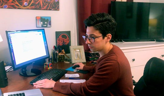 In this March 25, 2020 image taken from video by Caillin Wells, neuroscientist Michael Wells works on the COVID-19 Pandemic Shareable Scientist Response Database in his home in Cambridge, Mass.