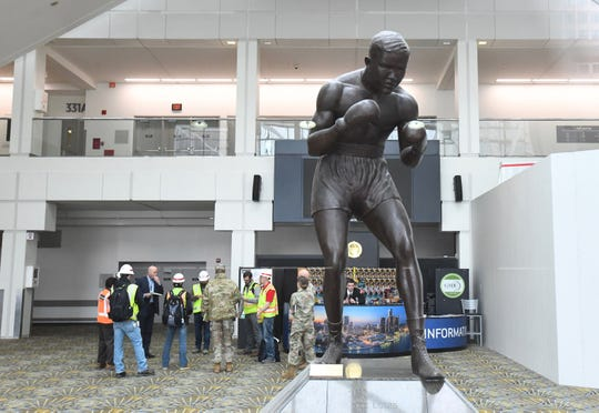 A group, several in military fatigues, gather by the Joe Louis statue at TCF Center on Monday, March 30 in Detroit.  The TCF Center will get 900 hospital beds from the U.S. Army Corps of Engineers for potential hospital overflow patients during the pandemic.