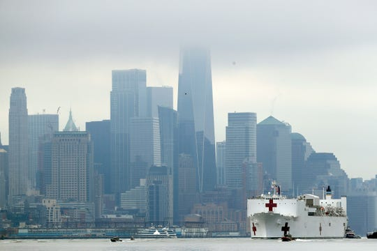 The Navy hospital ship USNS Comfort passes lower Manhattan on its way to docking in New York, Monday, March 30, 2020.